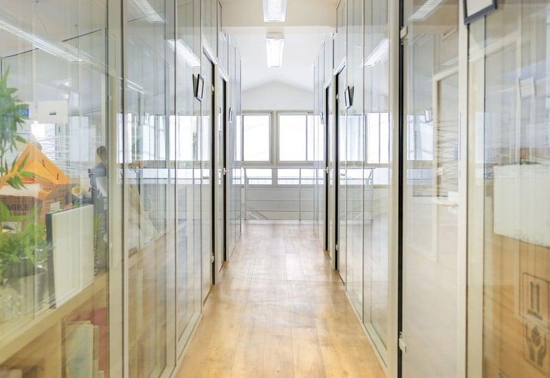 Couloir de bureaux avec des cloisons vitrées toute hauteur